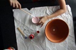 A child's hand paints a flower pot pink. White background.