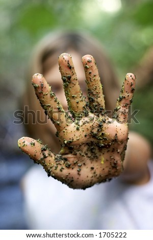 A child\'s hand with paint and grains of sand and dirt, in the stop position, focus on the hand, very shallow depth of field