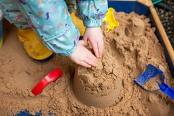 A child's hands can be seen building a sandcastle in a sand pit. The child is wearing bright and fun outdoor clothing and yellow wellington boots. A blue spade lays on the sand in the bottom left.