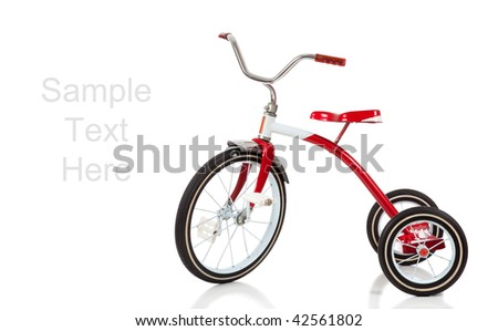 A child's red tricycle on a white background with copy space