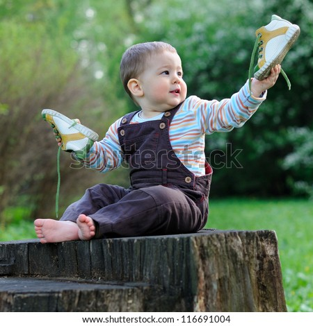 A child sits on a large tree stump with bare feet and playing shoes. Sunny summer day