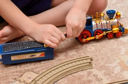 a child sits on the floor and repairs a toy train