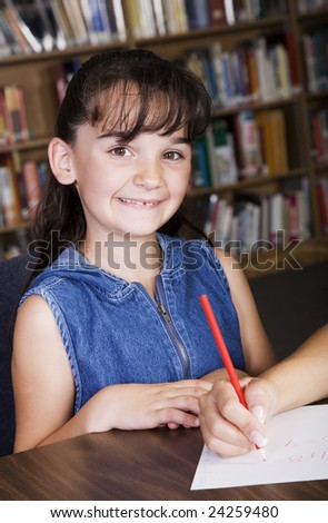 A child smiling from her desk in the school library.