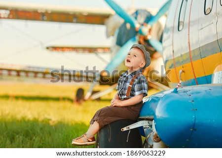 A child stand near an old plane and dreams of becoming a pilot when he grows up. The concept of choosing a future profession ストックフォト ©