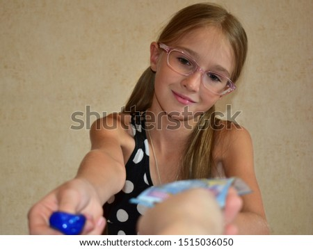 A child starts a small business. Girl makes and sells slides.