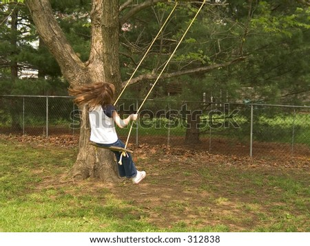 child swings on an old fashioned tree swing in the backyard