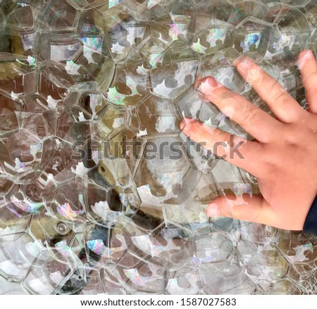 A child touches a pile of bubbles