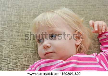 A child watches a cartoon on the TV lying on the couch, close-up.
