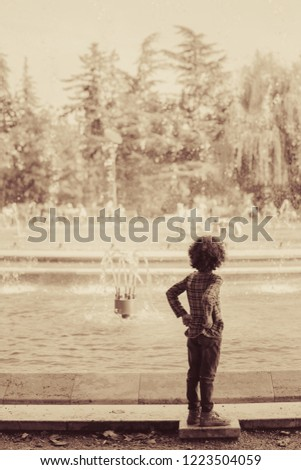 A child watching the musical fountain in Margaret Island (Margitsziget), Budapest, Hungary. Vintage effect photo