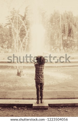 A child watching the musical fountain show in Margaret Island (Margitsziget), Budapest, Hungary. Vintage effect photo