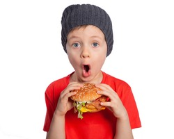 A child with a hamburger in his hands is surprised. Blue-eyed European boy 6 years old is going to eat fast food. Happy child. Snack. Favorite children's food.