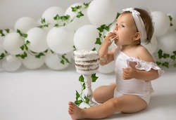 A child with an appetite eats a birthday cake for his first birthday. Festive decor made of balloons and trailing ivy.