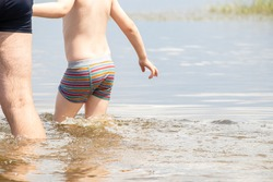 a child with dad goes into the river to swim in summer in Ukraine, swimming in the river