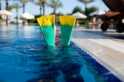 a child with fins in the pool. Fins on the background of the pool. Flippers