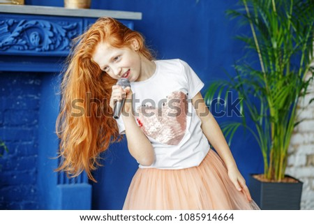 A child with long hair sings a song into the microphone. The concept is childhood, lifestyle, music, singing, listening, hobbies. #1085914664