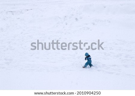 A child with winter clothes walking in a snowfield Stock photo ©