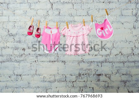 A children's pink bodik, a bib, a dress and red shoes for a girl, dry on a rope against a white brick wall. #767968693