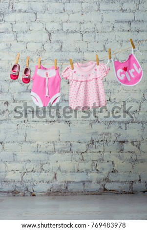 A children's pink bodik, a bib, a dress and red shoes for a girl, dry on a rope against a white brick wall. #769483978