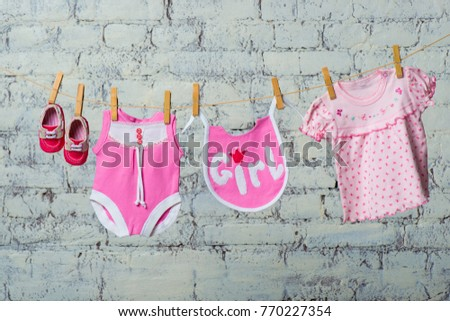 A children's pink bodik, a bib, a dress and red shoes for a girl, dry on a rope against a white brick wall. #770227354