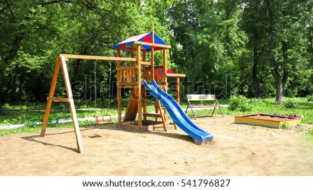 A children's playground, a slider located on the sand.
