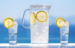 A chilled glass jug and two chilled glasses filled with cold water, ice cubes and lemon slices under bright sun light in front of a blurry sea view