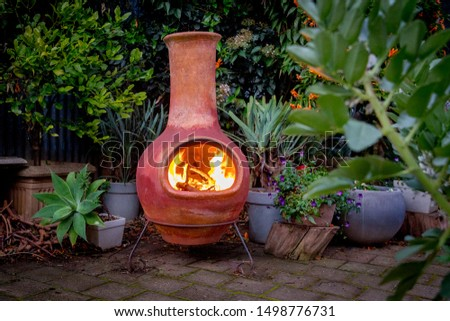 A Chimenea in the backyard.  A backyard fire place surrounded by plants. #1498776731