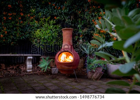 A Chimenea in the backyard.  A backyard fire place surrounded by plants. #1498776734