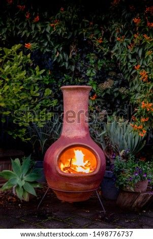 A Chimenea in the backyard.  A backyard fire place surrounded by plants. #1498776737