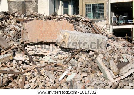 A chimney in the midst of large pile of rubble.