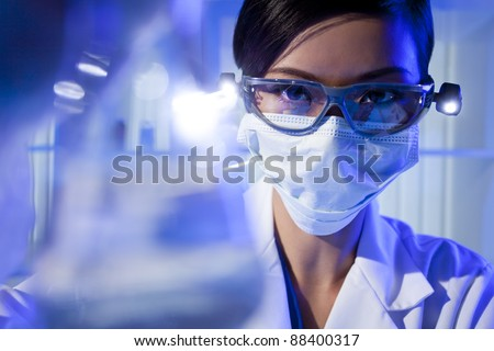 A Chinese Asian female medical or scientific researcher or doctor looking at a flask of clear liquid in a laboratory.