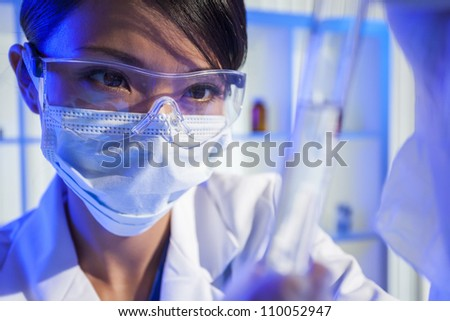A Chinese Asian female medical or scientific researcher or doctor looking at a test tube of clear liquid in a laboratory.