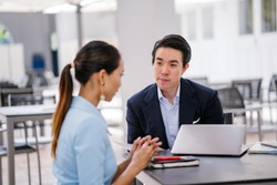 A Chinese Asian manager in a suit has a meeting with his colleague, a woman in a pale blue suit. He is conducting a performance appraisal during this meeting. They are smiling and talking.