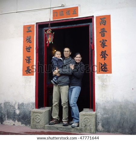 A chinese family photo, father,mother and baby, with a chinese style door. Photo by film.