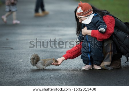 A Chinese mother Holds her baby wearing a winter jumpsuit, gloves and a fox hat as she feeds a brown squirrel which eats from her hand In Princes Street Gardens, Edinburgh, Scotland, United Kingdom