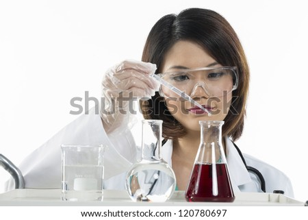 A Chinese scientific researcher looking at a liquid solution. Isolated on white background. - stock photo