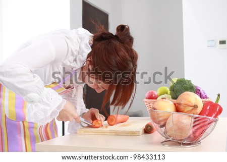 A Chinese woman is cooking  with various kinds vegetable.