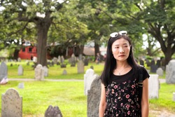 A chinese woman looking somber in the burying point cemetery in Salem Massachusetts.