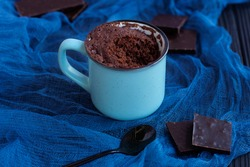 a chocolate cupcake in a mug is cooked in the microwave. Selective focus. In the background are pieces of dark chocolate and a black spoon on blue azure gauze. Fast, easy cooking concept.
