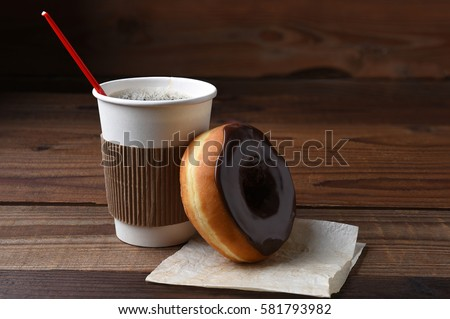 A chocolate frosted donut or doughnut leaning on a hot cup of fresh brewed coffee.