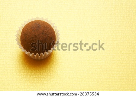 A chocolate truffle on gold background in the left