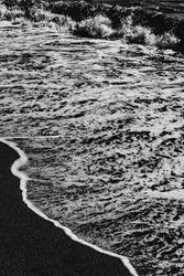 A choppy sea rolls over the sandy shore. Black and white photo.