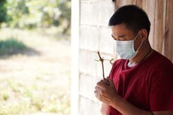 A Christian Asian man wearing hygienic mask is praying for God to save everyone from the global COVID-19 epidemic or coronavirus outbreak. Concept  for faith, Love in Jesus to all mankind
