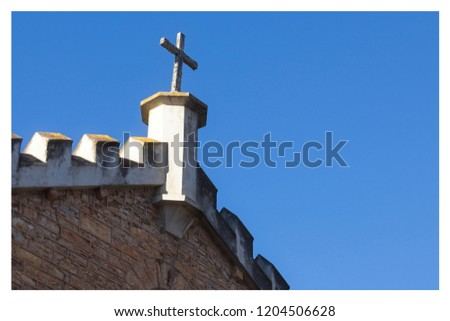 A Christian background image featuring a stone cross isolated on a blue sky. This image can be used to represent Christianity or religion.
