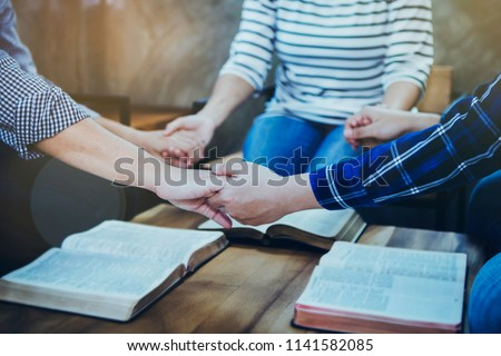 A christian group holding hands and together over blurred bible on wooden table, Christian background, fellowship or bible study concept