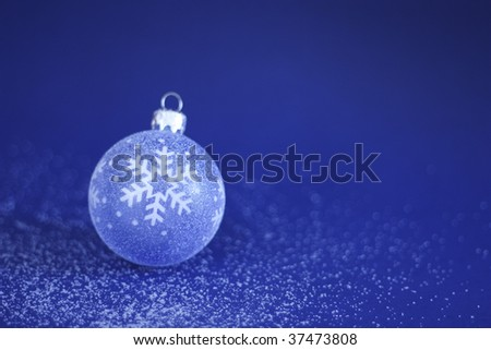 A Christmas Bauble on light sprinkle of snow with a blue background