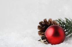 A Christmas border and background with red bauble, fir cone and green branch, nestling in white fake snow in lower right corner.  Twinkling stars in background above.