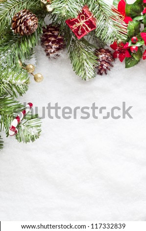 A Christmas border to left and top of frame consisting of artificial foliage, real pine cones and decorative ornaments, sprinkled with snow on a fake snow background.   Snow provides copy space.
