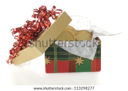 A Christmas gift box filled with homemade sugar cookies.  On a white background.