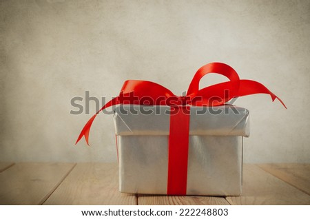 A Christmas gift box with closed lid, wrapped in silver paper and tied to a bow with a red satin ribbon.  Placed on a weathered old wooden table with copy space to left and above. Vintage style.