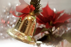 A Christmas gold bell with bright red bow against red, white and silver Christmas decorations